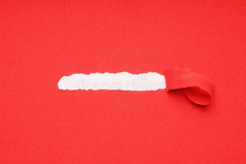 A casca afastado rasgou o papel vermelho para revelar embaixo o espaço escondido da cópia fotos de stock