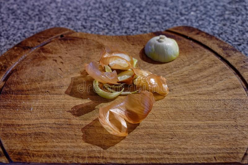 Casca da cebola e as sobras de uma cebola que senta-se em uma placa de desbastamento de madeira fotos de stock royalty free
