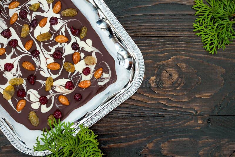 Casca do chocolate do feriado com frutos e as porcas secados em um fundo de madeira escuro Vista superior Receita da sobremesa pa imagem de stock royalty free