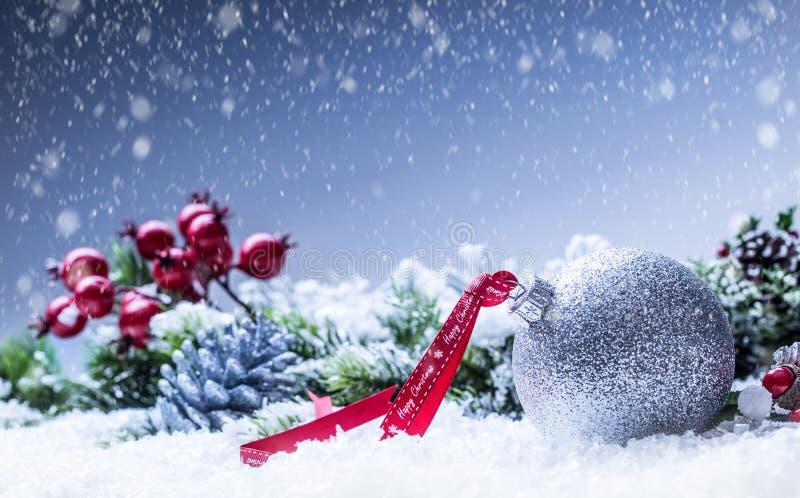 Cascabeles de las bolas de la Navidad Cinta roja con feliz Navidad del texto Fondo y decoración del extracto Nevado foto de archivo
