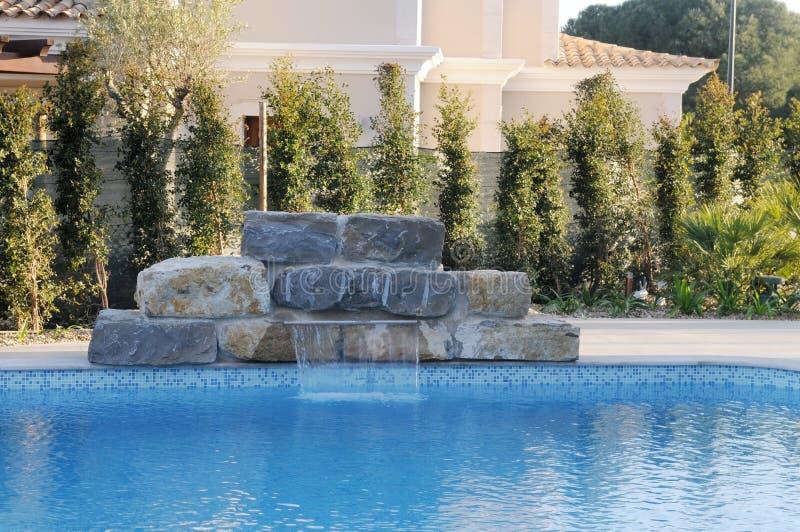 Cascada artificial sobre la piscina azul - luz del día imágenes de archivo libres de regalías