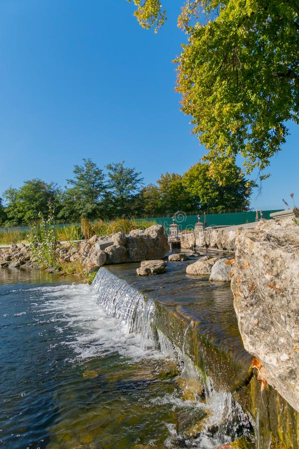 Cascada de conexión en cascada con los cantos rodados de piedra a lo largo de los bancos, en un parque debajo de un árbol Mezhygi foto de archivo