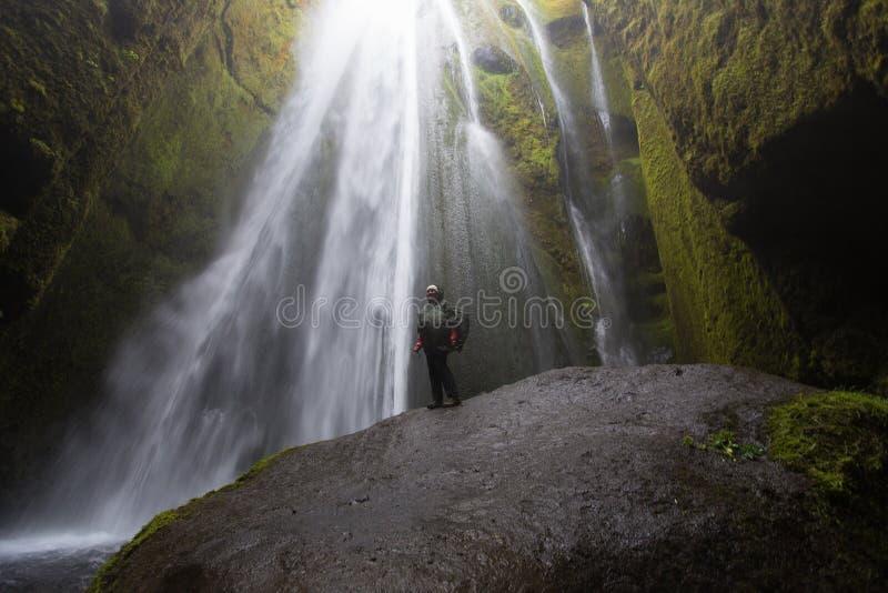 Cascada de Gljufrafoss con la mujer activa fotografía de archivo