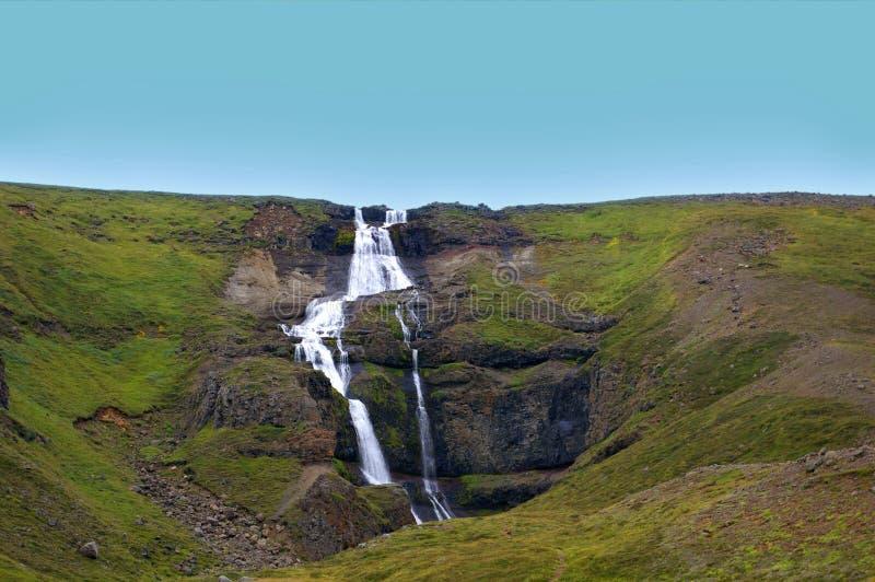 Cascada de la cascada en una colina verde imagen de archivo