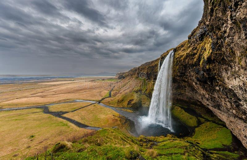 Cascada de Seljalandsfoss en Islandia Uno de la cascada famosa del ost en Islandia Cielo nublado foco hacia números más inferiore imagen de archivo libre de regalías