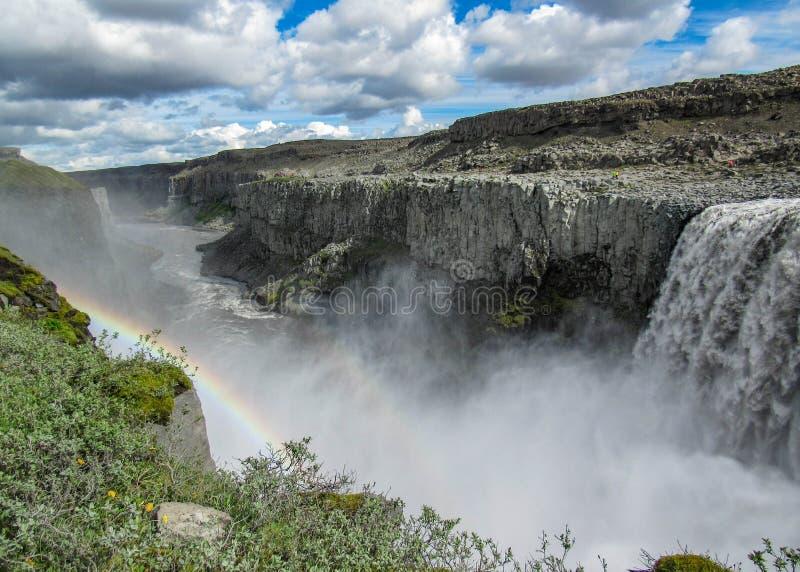 Cascada Dettifoss con el arco iris, las columnas negras del basalto y el espray de agua en día de verano soleado Islandia septent fotos de archivo