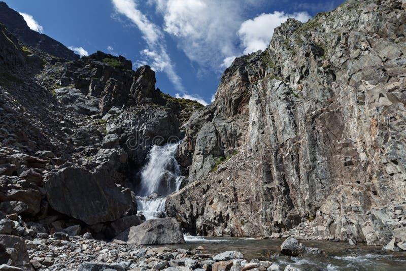 Cascada en el río de la montaña y los acantilados escarpados imagenes de archivo