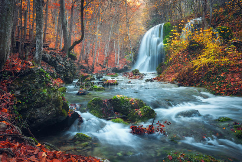 Cascada hermosa en bosque del otoño en montañas crimeas en el sol fotos de archivo
