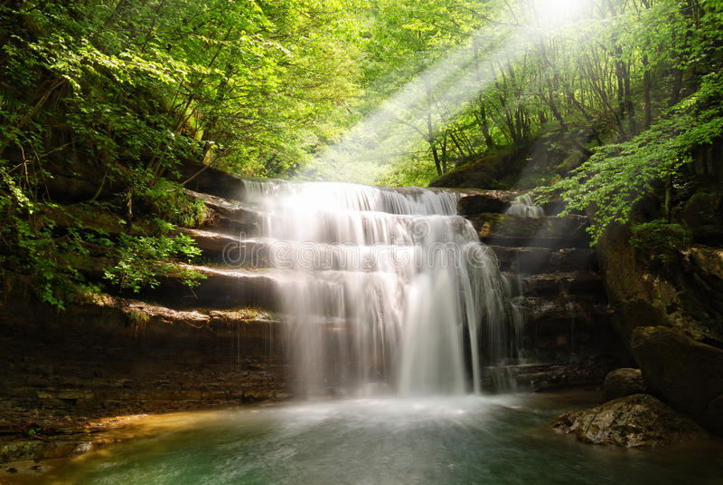Cascada iluminada por la sol fotografía de archivo libre de regalías