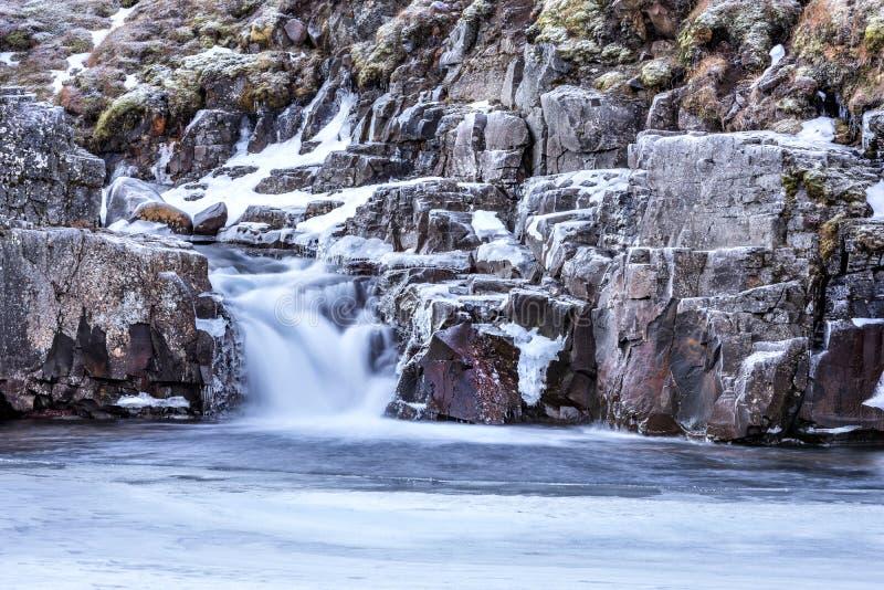 Cascada Nevado en montañas del ` s de Islandia fotos de archivo