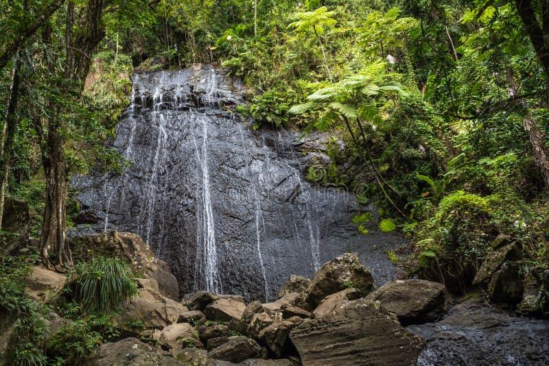 Cascada que conecta en cascada sobre una cara enorme de la roca en selva tropical fotografía de archivo