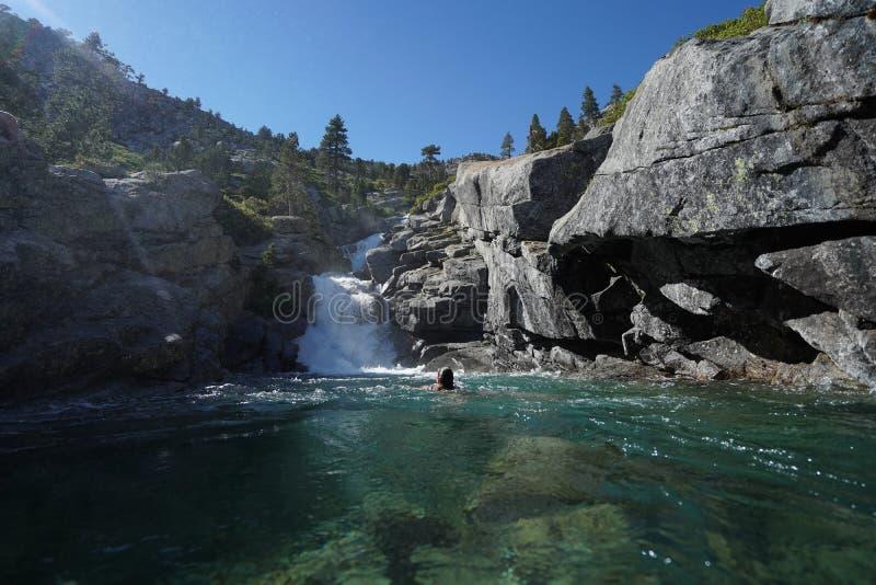Cascada que fluye abajo de los acantilados rocosos a una charca con la natación femenina cerca del lago Tahoe, CA foto de archivo