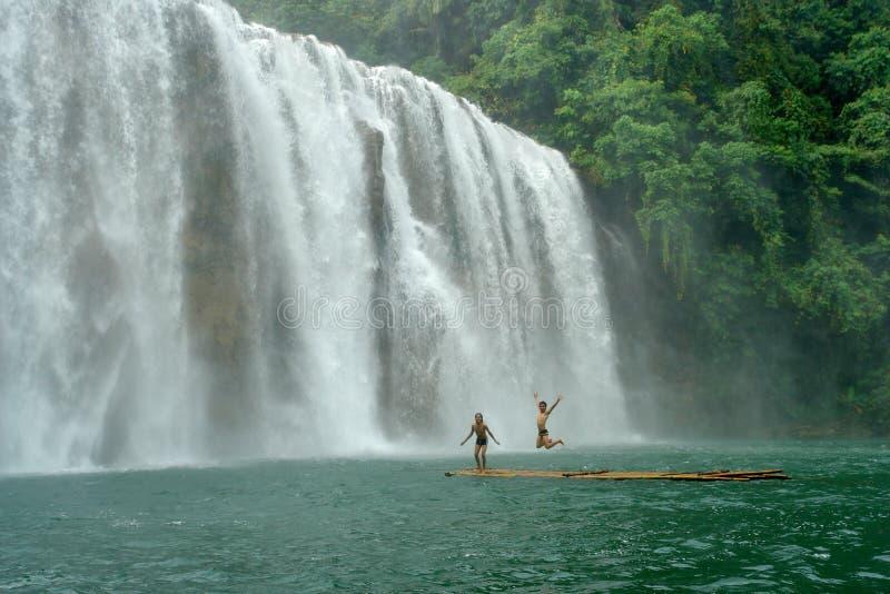 Cascada tropical con los muchachos en balsa. foto de archivo