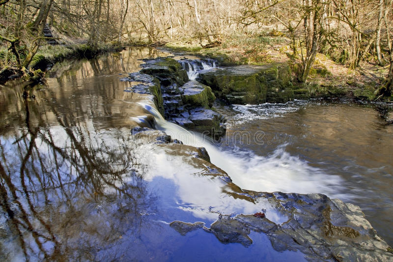 Cascada y cascada en los árboles reflectores de Neath del río y los cielos azules fotos de archivo libres de regalías