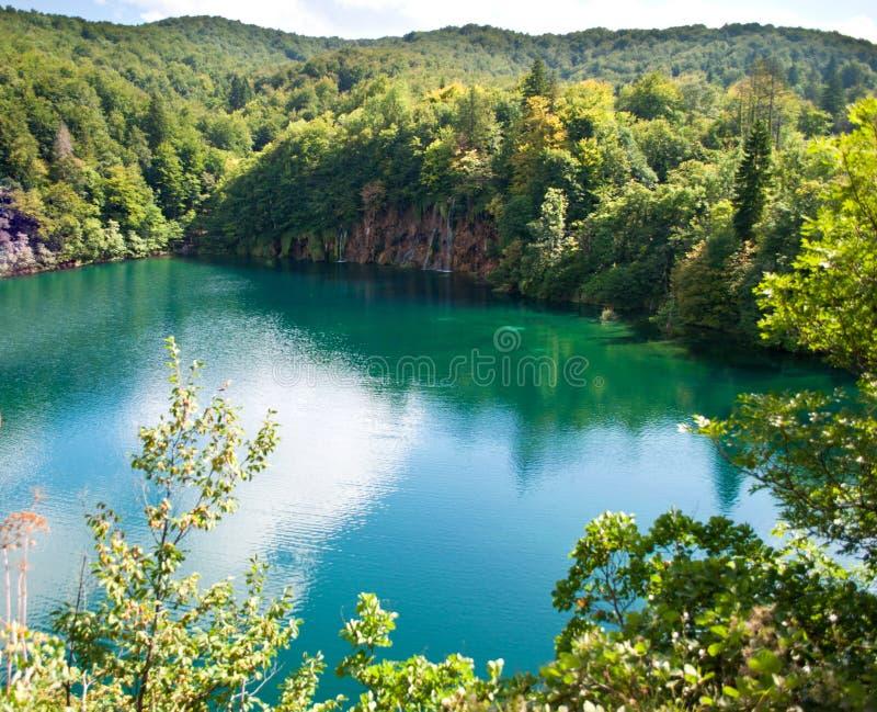 Cascada y lago con agua esmeralda transparente fotografía de archivo libre de regalías