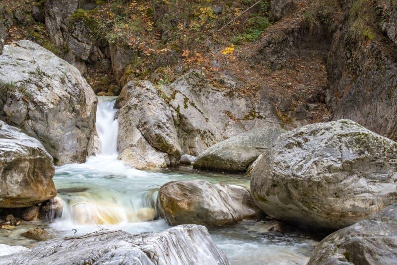 Cascada y río entre los cantos rodados de piedra en un bosque del otoño de la montaña fotos de archivo libres de regalías