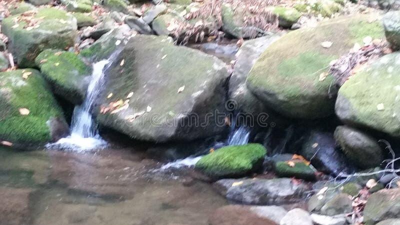 Cascade à écriture ligne par ligne circulant sur des roches photographie stock libre de droits