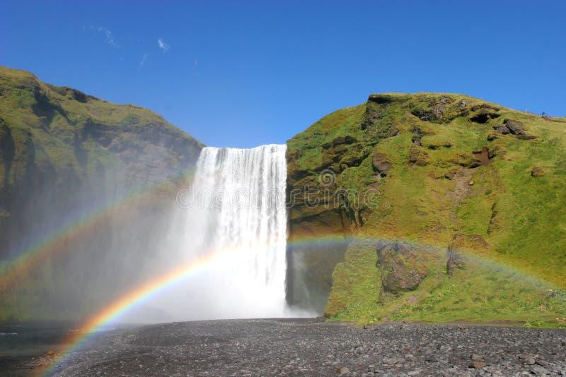 Cascade à écriture ligne par ligne de l'Islande et double arc-en-ciel photographie stock