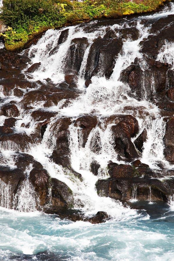 Cascade à écriture ligne par ligne sur le fleuve de montagne en Islande image stock