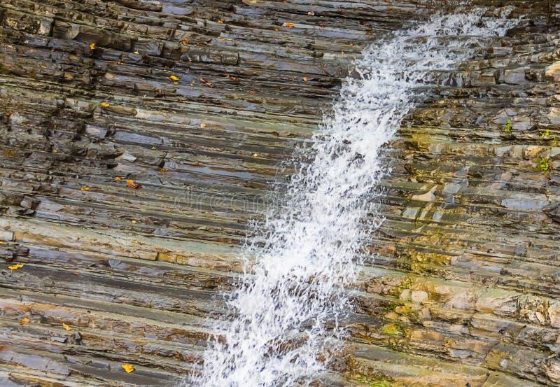 Cascade de courant de l'eau blanche le long de la montagne humide à nervures photographie stock libre de droits