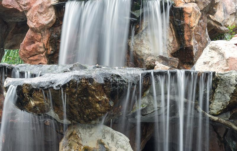 Cascade entrant au-dessus des roches dans le jardin photos stock