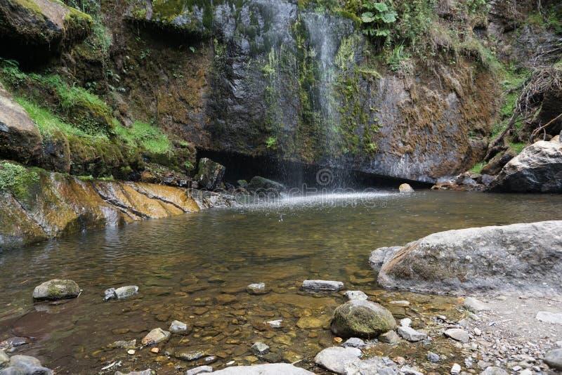 Cascade et lac peu profond avec des roches image libre de droits