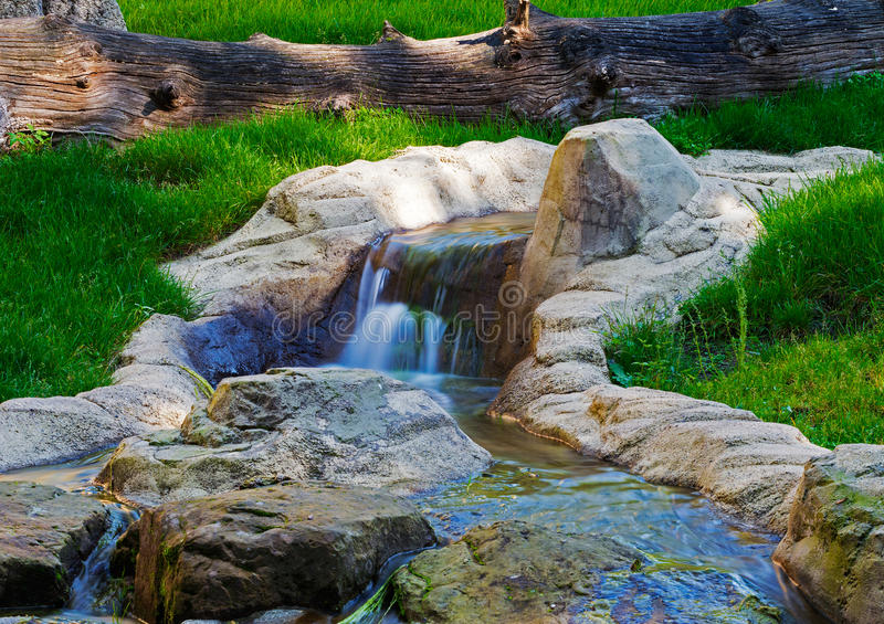 Cascade sur The Creek traversant l'herbe verte photographie stock