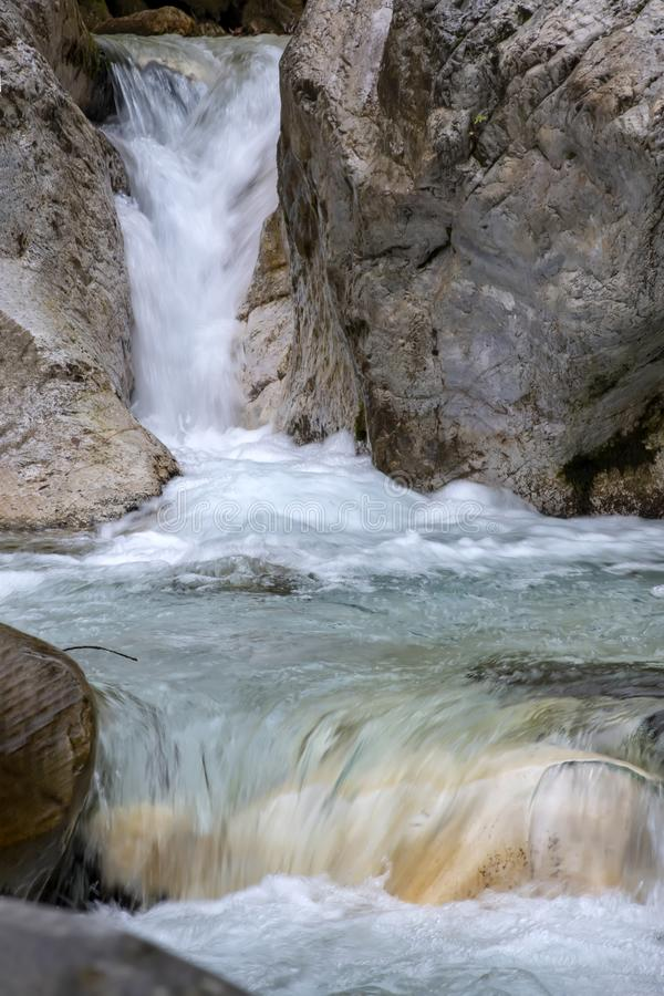 Cascades of a mountain stream flowing between huge boulders stock image