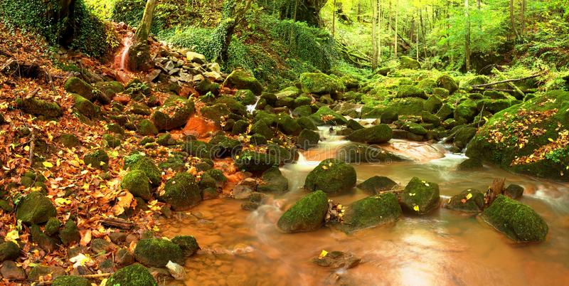 Cascades in rapid stream of mineral water. Red ferric sediments on big boulders stock photography