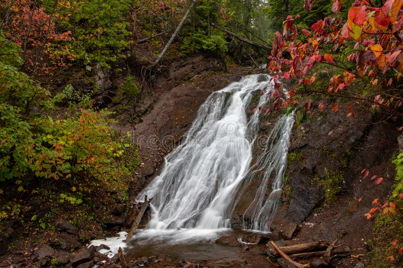 Autumn at Jacobs Falls in the Upper Peninsula of Michigan, USA. Cascading water flows rapidly over Jacob's Falls near Eagle River Michigan. Autumn colors royalty free stock photography