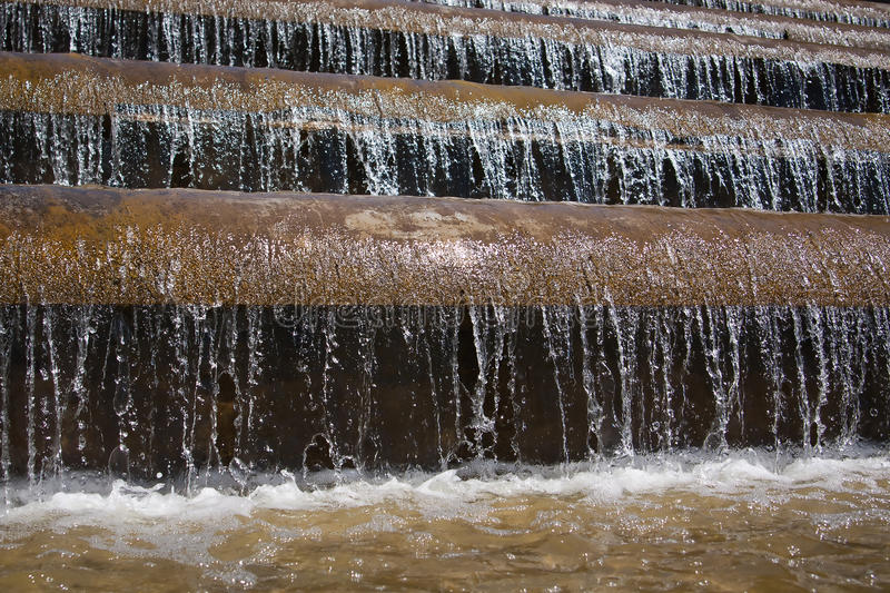 Cascading waterfall. Falling water in the fountain macro background royalty free stock images