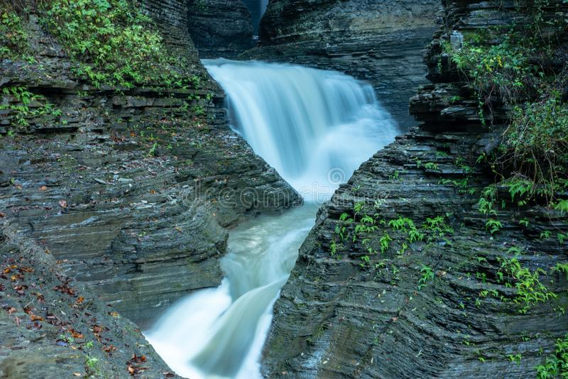 Cascading waterfall into Glen creek in Watkins Glen State Park New york. Warm autumn day. Daylight highlights the rocks on both royalty free stock images