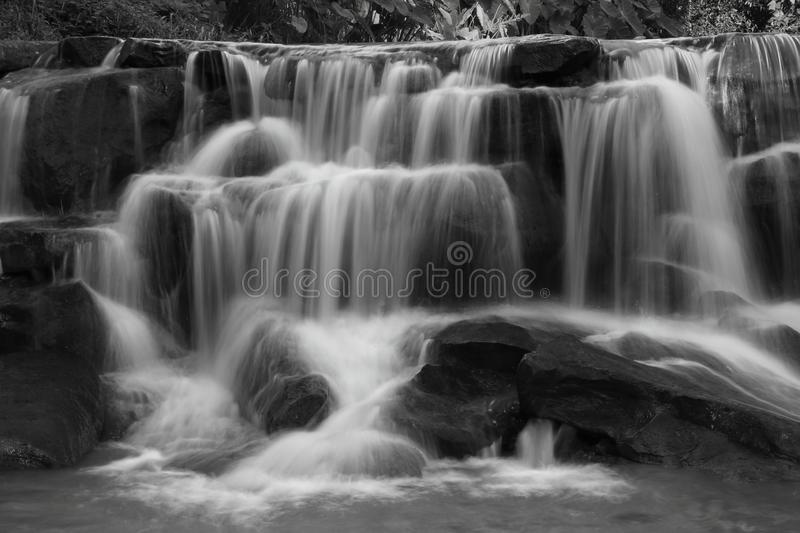 Cascading waterfall in rainy season deep inside the tropical forest of Thailand in black and white color royalty free stock image