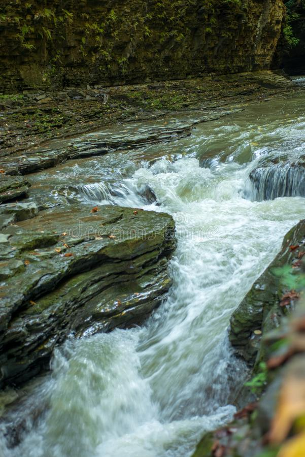 Cascading waterfall rushes between rock outcrops on Glen creek in Watkins Glen State Park stock images