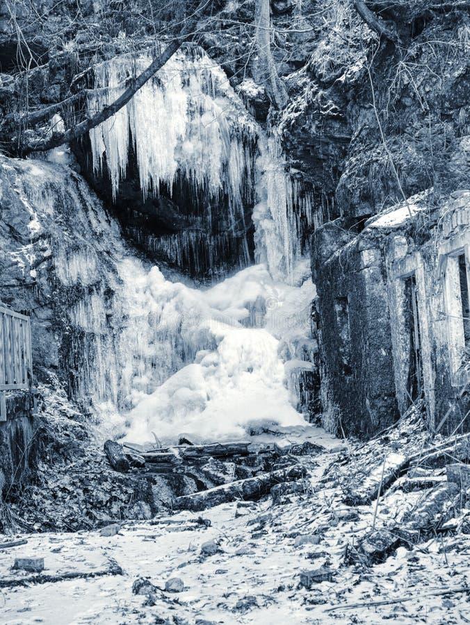 Cascata congelata fra le rocce Cascata caduta di muggito del ghiacciolo, fotografia stock libera da diritti