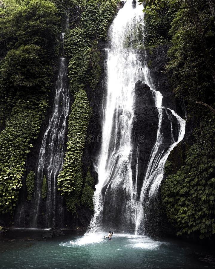 Cascata da cachoeira na floresta úmida tropical com pares no amor que banha-se embaixo imagens de stock royalty free