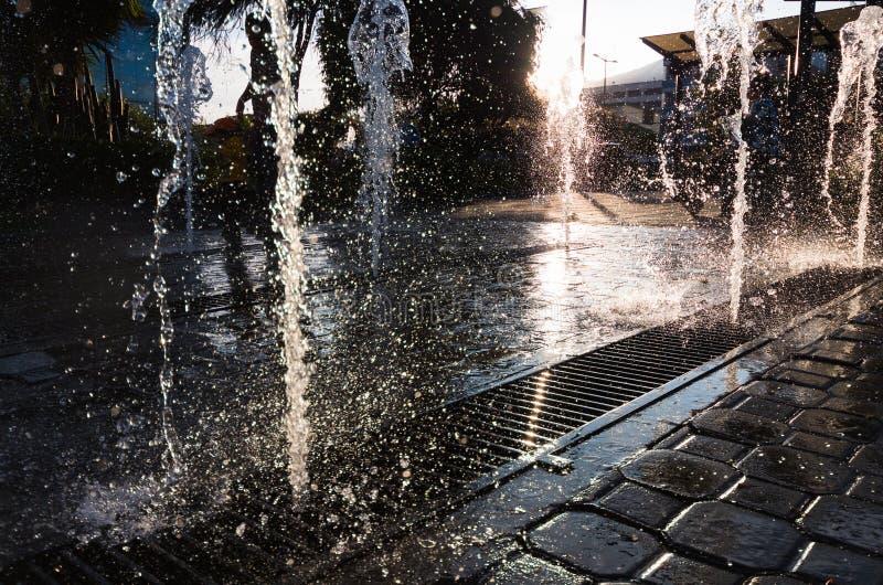 Cascata del beutifull e moderna con il sole nella parte posteriore Ballare delle gocce di acqua immagine stock