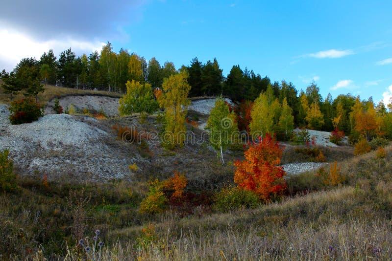 Cascata dos montes da pedra calcária cobertos com as árvores com folha do outono fotografia de stock royalty free
