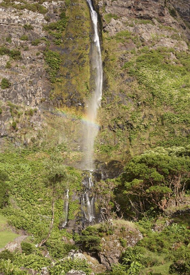 Cascata ed arcobaleno nell'isola del Flores, Azzorre Poco fa Bacalhau fotografia stock
