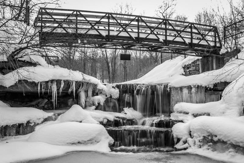Cascata ghiacciata bianca nera sotto il ponte fotografie stock
