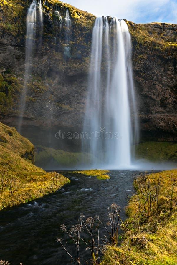 Cascata maestosa che cade un fianco di una montagna ripido in Islanda fotografie stock