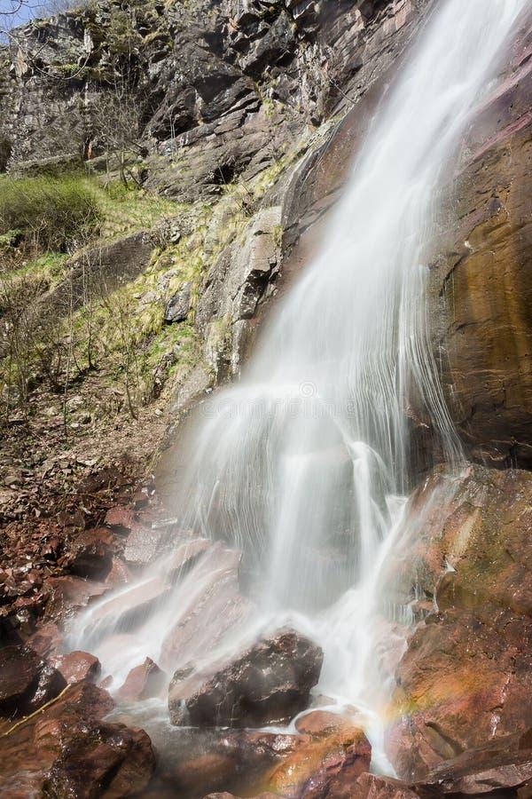 Cascata soleggiata potente che spruzza sulla roccia che crea un arcobaleno fotografia stock