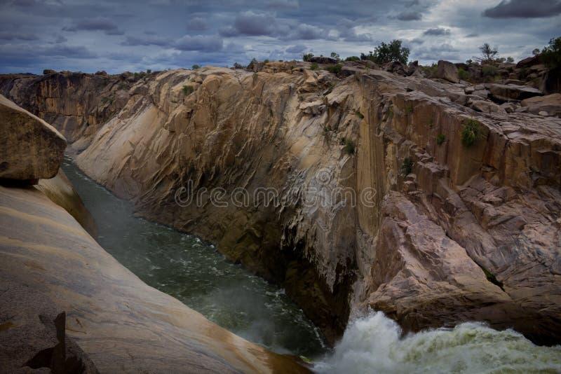 Cascata in un canyon ripido sotto un cielo tempestoso fotografia stock libera da diritti