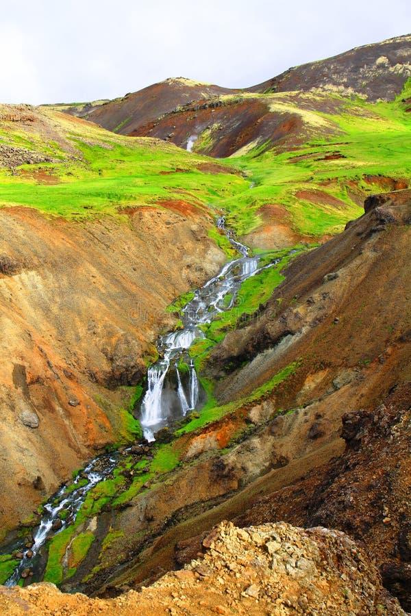 Cascata vicino al fiume termico della sorgente di acqua calda di Reykjadalur immagine stock