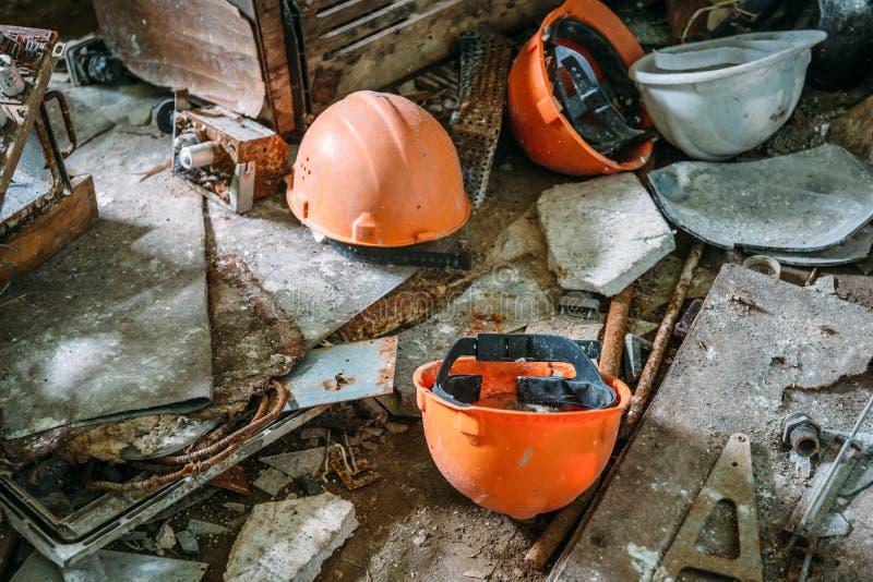 Caschi arancio sul pavimento sporco in fabbrica abbandonata, concetto rovinato di economia immagini stock