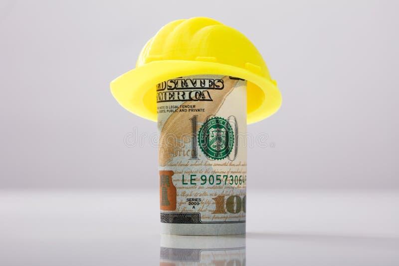 Casco amarillo sobre rodado encima de billete de banco americano fotos de archivo libres de regalías