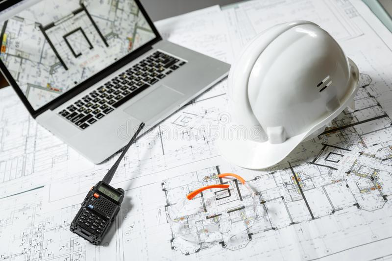 Casco bianco, computer portatile con i disegni, vetri e walkie-talkie con e modelli su una tavola immagine stock