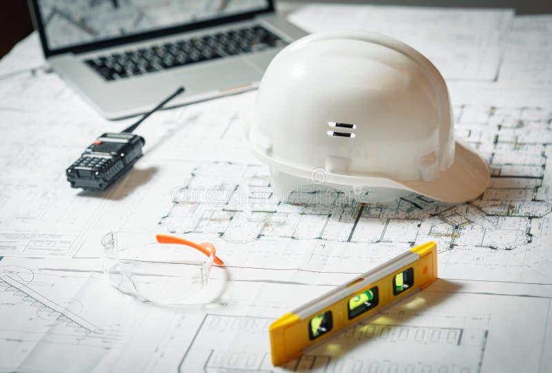 Casco bianco, computer portatile con i disegni, vetri e walkie-talkie con e modelli su una tavola immagini stock libere da diritti