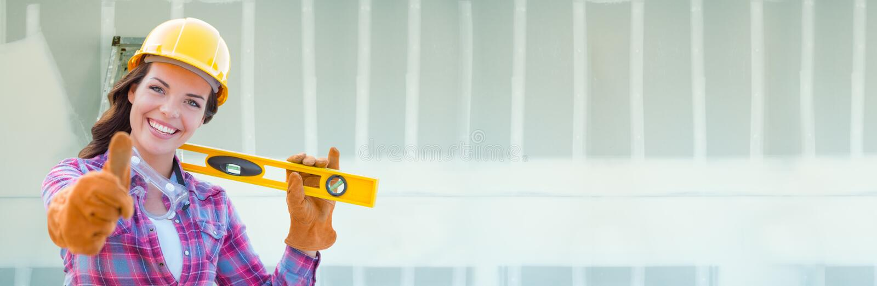 Casco d'uso dell'appaltatore femminile contro il fondo dell'insegna del muro a secco con la scala fotografia stock