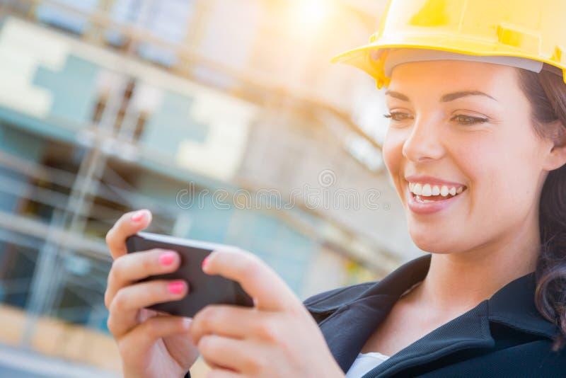 Casco d'uso dell'appaltatore femminile sul sito che manda un sms con la cellula Pho fotografia stock libera da diritti